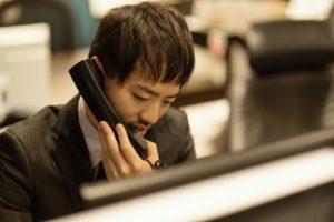 電話しながらパソコンを操作する男性